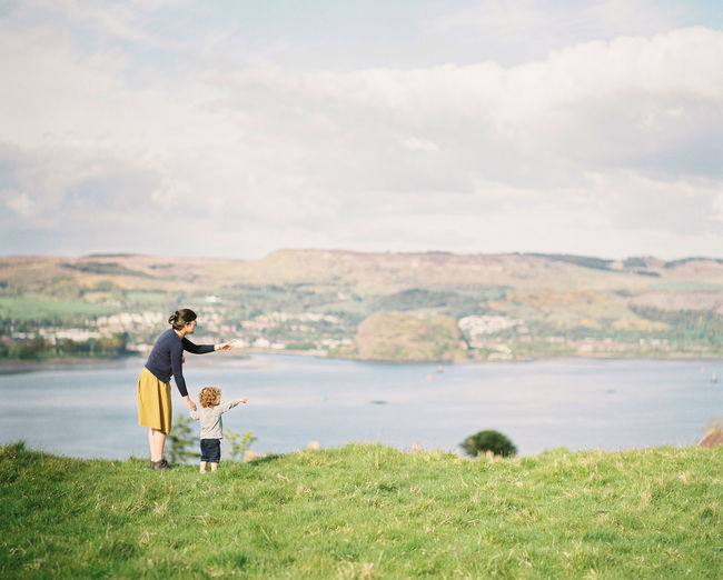Mother with son standing on land against lake