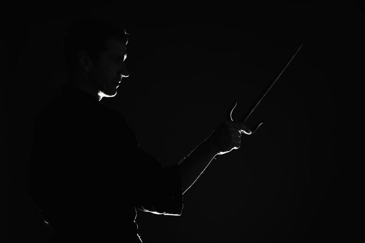 Low angle view of silhouette man against black background