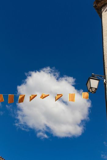 Low Angle View Of Flags By Lamp On Cropped Building Wall