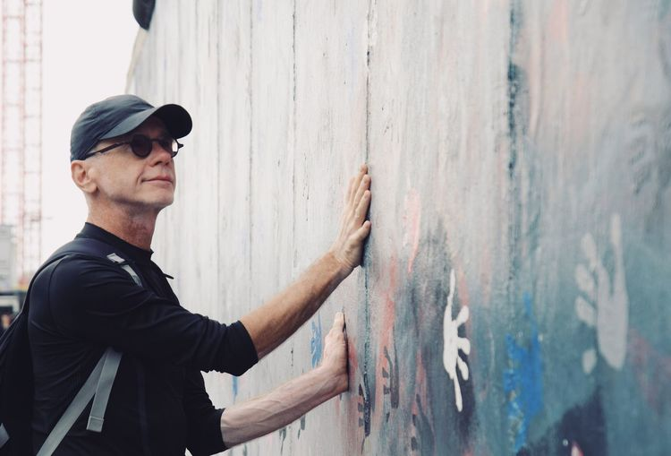 Side view of mature man touching graffiti wall