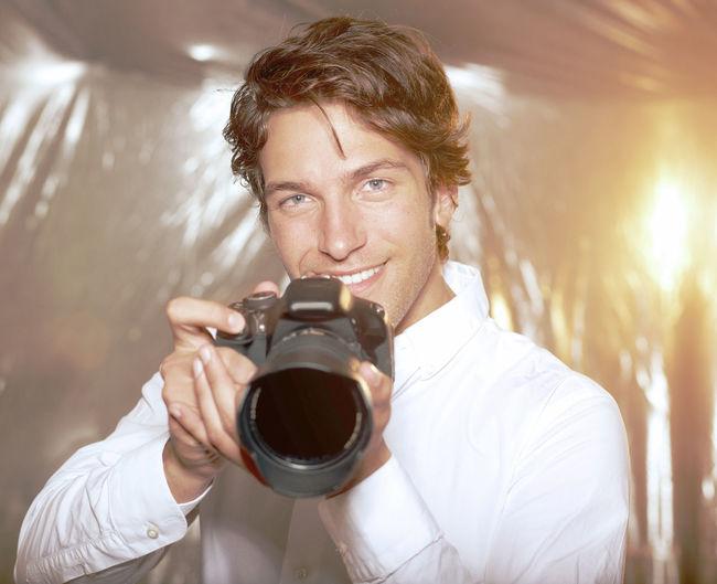 Portrait of handsome man holding camera