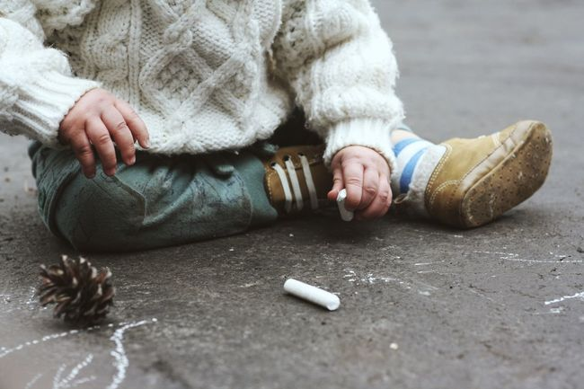 Baby Chalk Check This Out Child Childhood EyeEm EyeEm Best Shots Feet Hands Holding Little One Person Outdoors Outside Pavement Person Pinecone Popular Photos Selective Focus Sitting Sweater Toddler