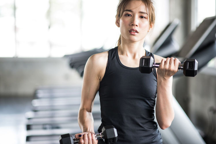 Adult Clothing Dumbbell Effort Exercise Equipment Exercising Front View Gym Healthy Lifestyle Lifestyles One Person Sport Sports Training Strength Vitality Weight Weight Training  Weights Women Young Adult