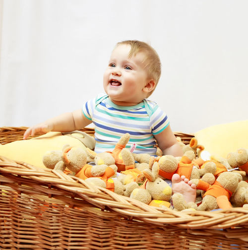 Cheerful baby boy sitting with toys in wicker basket