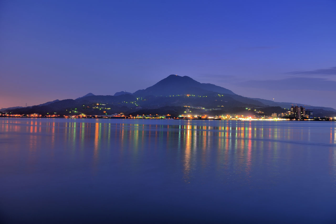 mountain, night, water, reflection, illuminated, no people, waterfront, outdoors, blue, scenics, lake, tranquil scene, nature, sky, beauty in nature, tranquility, mountain range, clear sky, sunset, architecture, building exterior