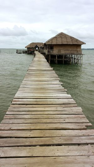 Wooden Bridge Over Water Kelong Outdoors Built Structure Architecture Roof Day Building Exterior No People Sky Nature The Week On EyeEm EyeEmNewHere Eye Em Nature Lover Thatched Roof Stilt House Water