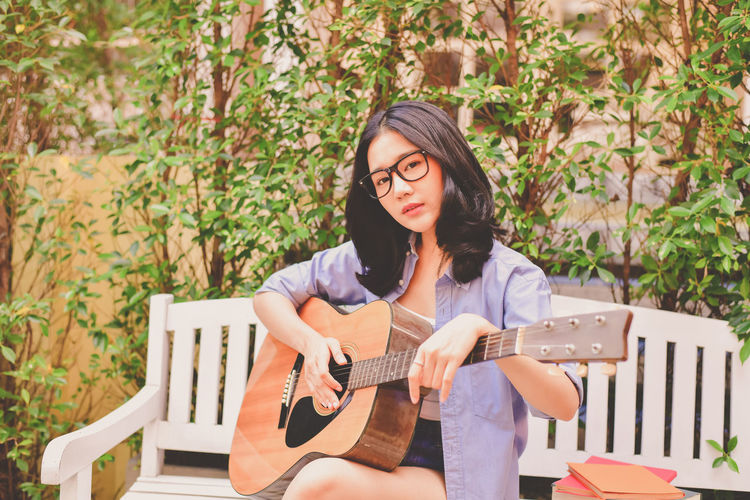 Acoustic Guitar Casual Clothing Day Front View Guitar Hairstyle Holding Leisure Activity Lifestyles Music Musical Instrument One Person Outdoors Plant Playing Plucking An Instrument Real People Seat Sitting String Instrument Women Young Adult Young Women