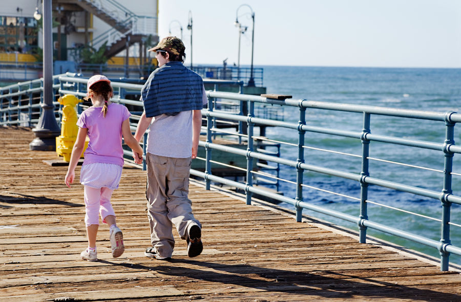 Brother & sister hold hands as they walk along the pier Brother Children Family Holding Hands Los Angeles, California Pier Rear View Sister Baseball Cap Casual Clothing Full Length Happiness Little Girl Outdoors Railing Real People Sea Teenage Boy Teenager Togetherness Two People Walking