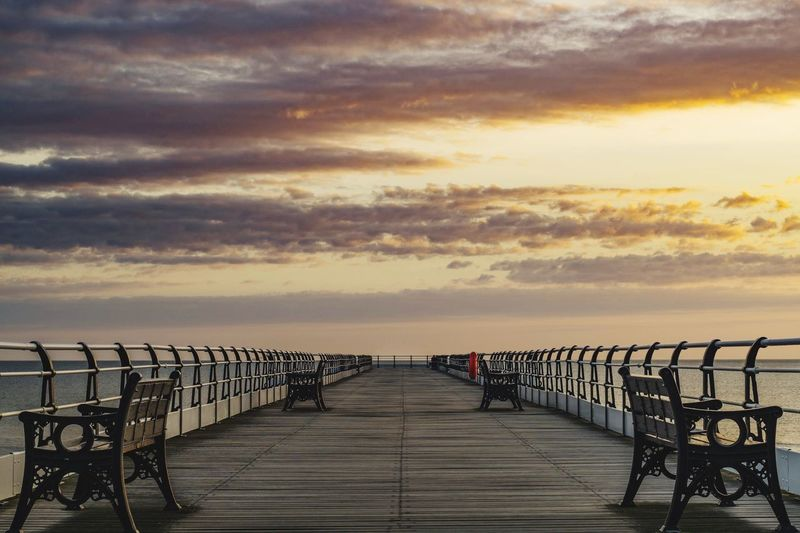 Empty Bench On Pier Over Sea Against Sky During Sunset