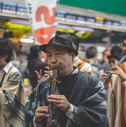 Close-up man playing flute in city