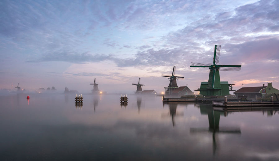 "The famous Dutch windmills at the ""Zaanse Schans"" Full Frame Sky Water Cloud - Sky Reflection No People Waterfront Sunset Fog Scenics - Nature Beauty In Nature Zaanse Schans Nederland Holland Dutch Dutch Landscape Windmills Traditional Windmill"