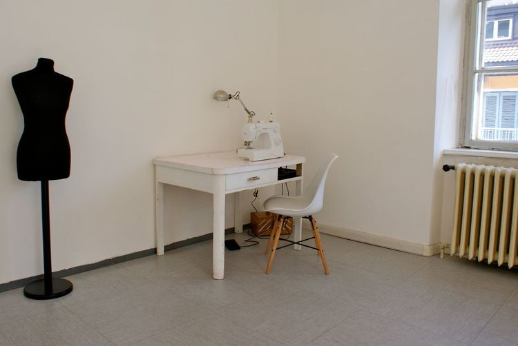 Sewing Machine On Desk With Mannequin Against Wall