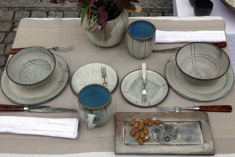 High angle view of crockery and almonds on outdoor table