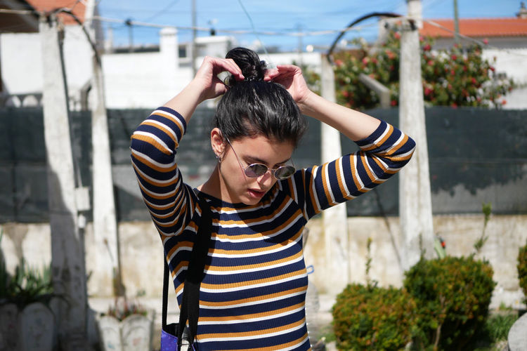 Young woman tying hair bun while standing in terrace