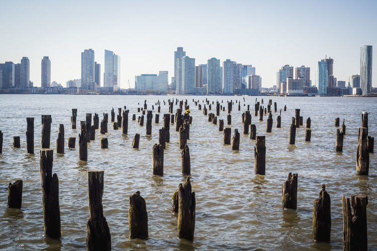 Wooden posts in sea against cityscape in new york city