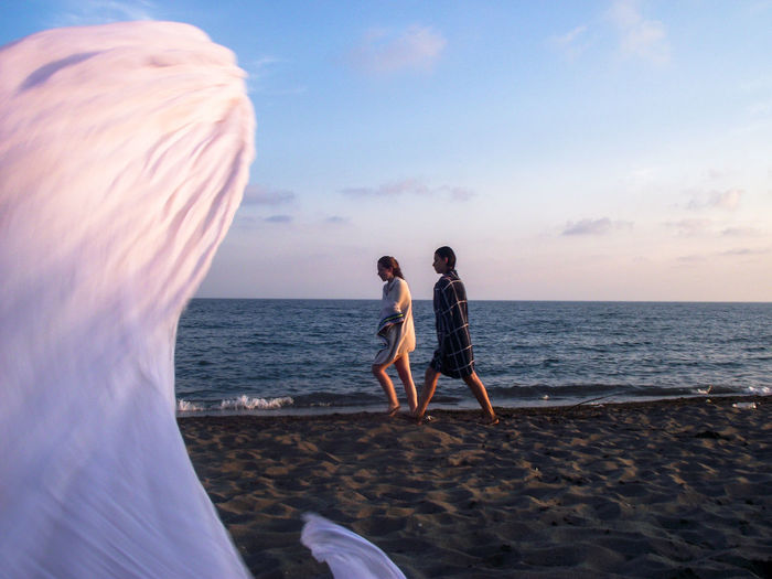 Friends With Towels Walking At Beach Against Sky During Sunset
