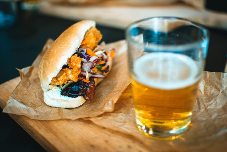 Close-up of chicken sandwich with beer glass on table