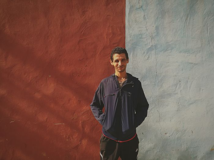 Portrait of smiling young man with hands on pockets standing against wall