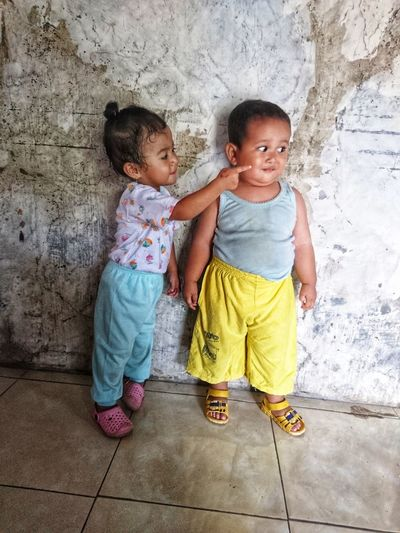 sister touching cheek of brother while standing against wall