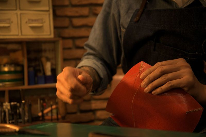 Midsection of man sewing leather in workshop
