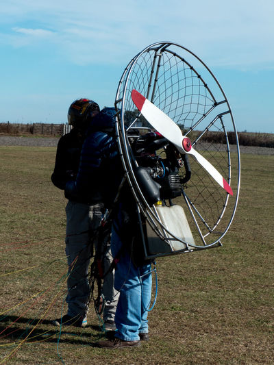 People with electric motor preparing for paragliding on land