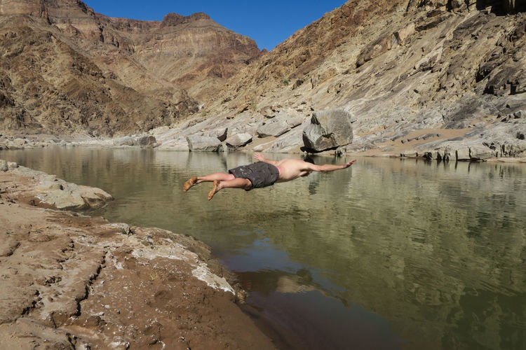 Male jumping into river for a swim Adventure Arid Climate Canyon Dive Jump Jumping Lake Let's Go. Together. Man Mid-air Mountain Mountain Range Namibia Nature One Person Outdoor Photography Outdoors Reflection River Shirtless Swim Water Wilderness