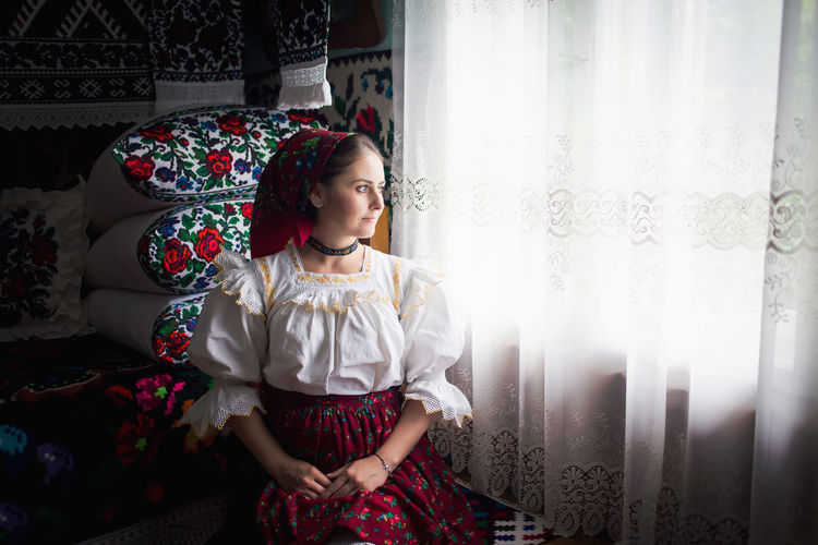 Thoughtful woman looking through window curtain