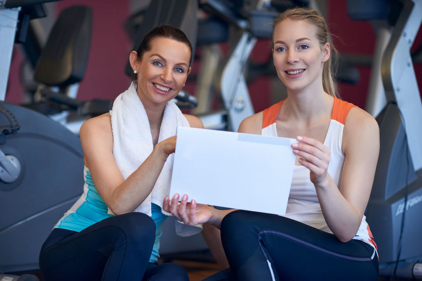 Two female athletes holding their traing plan Coach Plan Sitting Athletes Best Ager Blond Casual Clothing Cheerful Exercise Plan Female Gym Happiness Healthy Lifestyle Indoors  Middle-aged Sitting Smiling Sports Sports Clothing Talking Togetherness Trainings Plan Women Young Adult Young Women