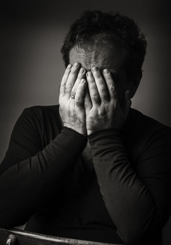 Depressed mature man covering face with hands while sitting at home