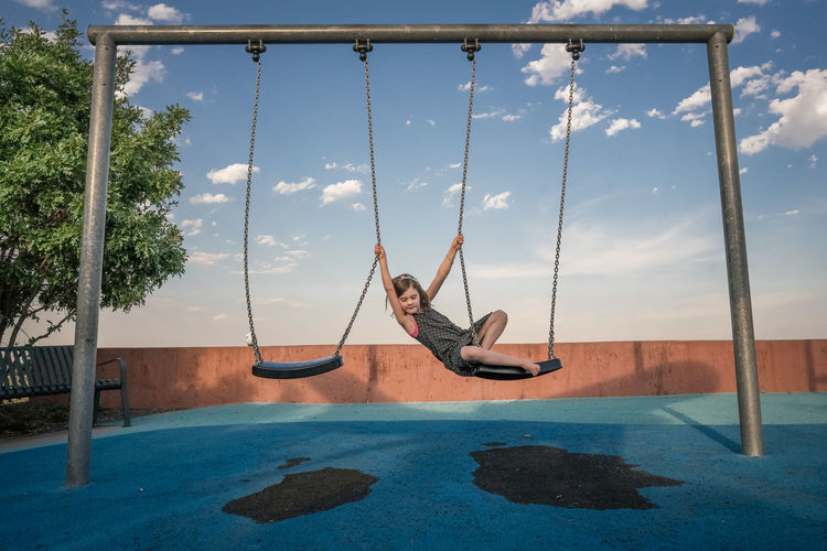 Person on swing in swimming pool against sky