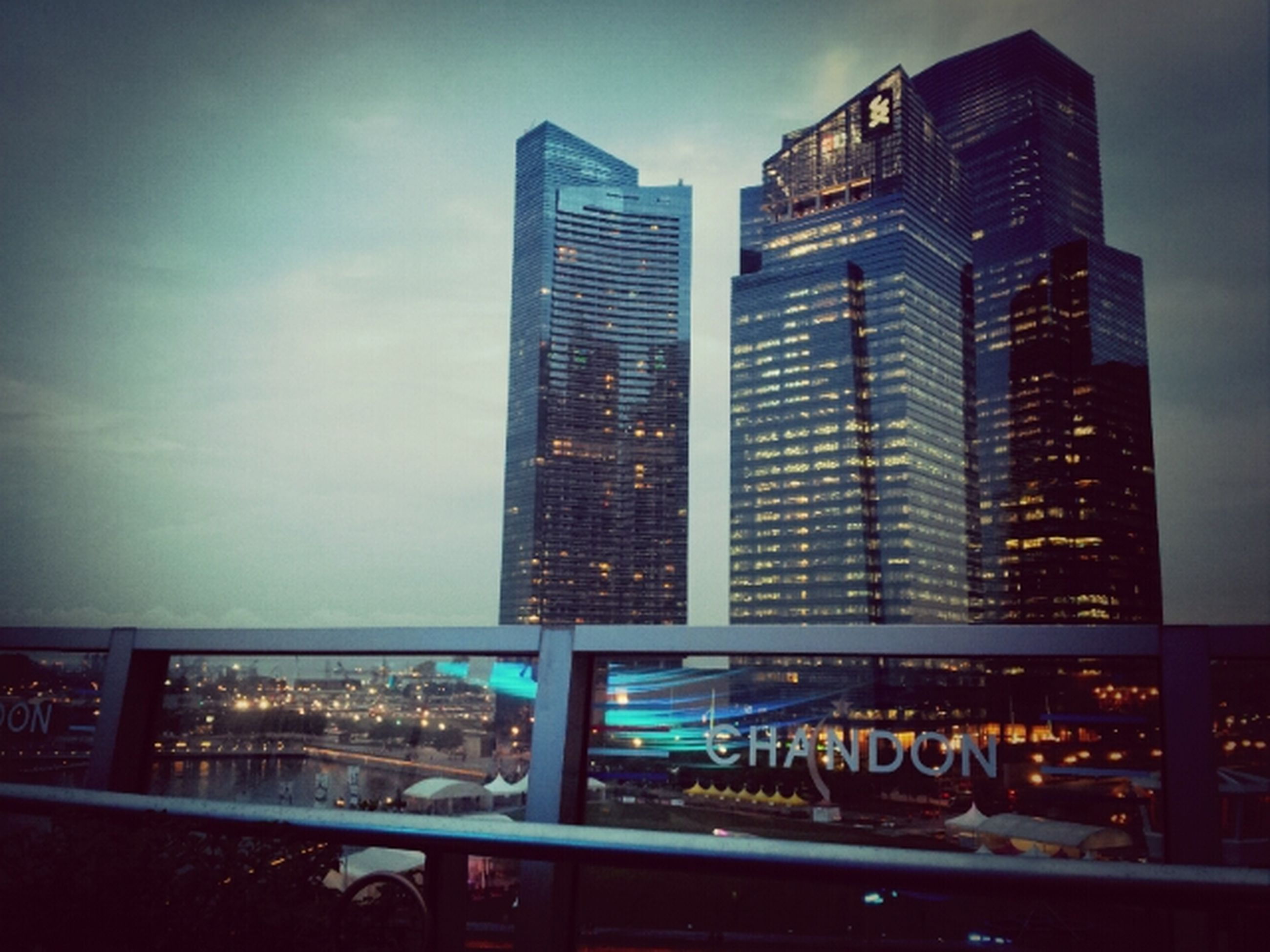 building exterior, architecture, city, built structure, skyscraper, sky, modern, office building, illuminated, cityscape, building, city life, glass - material, night, incidental people, tall - high, land vehicle, window, urban skyline, outdoors