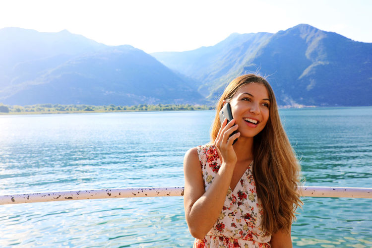 Cheerful Young Woman Using Phone While Standing Against Lake And Mountains