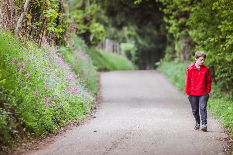 Full length of boy walking on road