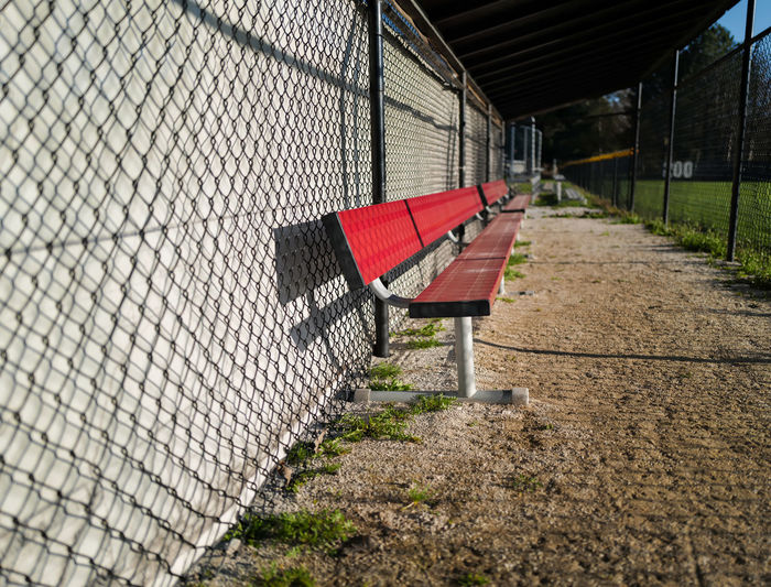 Empty red baseball dugout bench