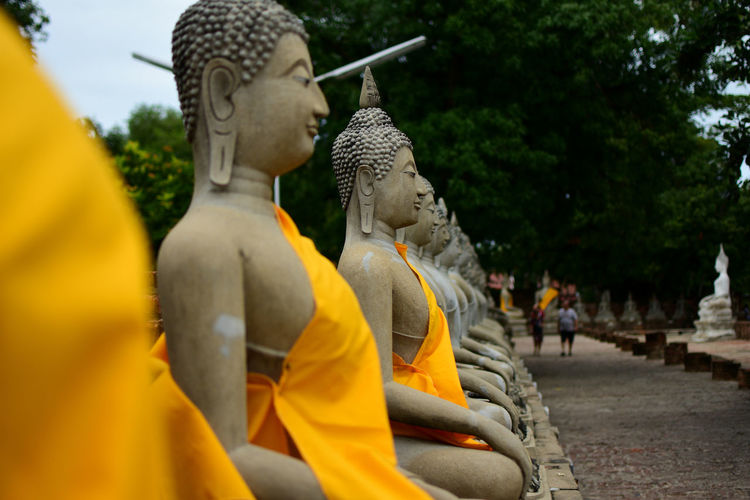 An ancient stone sculpture in Wat Yai Chaimongkhon, Ayutthaya, Thailand. Statue Sculpture Religion Outdoors Travel Experience Budhism Budha Robe Ayutthaya Scenics Wanderlust Travel Thailand Orange Color Travel Photography Wat Yai Chai Mongkhon Travel Destinations Line Up Togetherness Solo Travel Budha