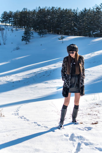 Snow Winter Cold Temperature One Person Leisure Activity Full Length Lifestyles Front View Young Adult Real People Standing Tree Day Nature Young Women Plant Sunlight Clothing Fashion Warm Clothing Outdoors
