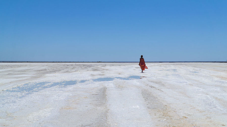 Rear view of woman walking against clear sky