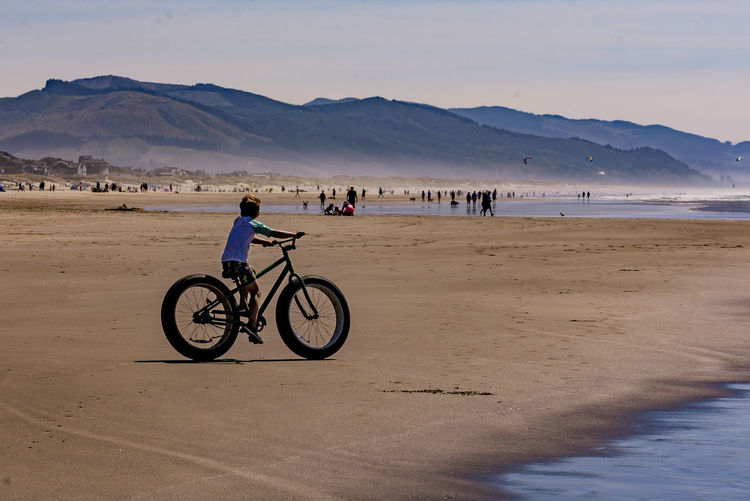Boy riding a fat tired sand bike on the beach. Riding Roller Coasters Wheel Beach Bicycle Boy Fat Large Group Of People Leisure Activity Lifestyles Mountain Nature Outdoors People Riding Sand Sea Tire Water