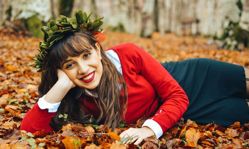 Portrait Of Smiling Young Woman Lying Down On Autumn Leaves