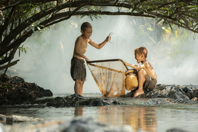Asia children glad fisherman on river stream / The boy friend happy funny laughing fishing with net and fish in hand at countryside of living life kids rural people Activity Background Beautiful Boy Casting Catch Caucasian Child Childhood Day Equipment Family Fish Fisherman Fishing Freshwater Fun Happiness Happy Hobby Kid Lake Landscape Leisure Life Lifestyle Little Male Man Men Nature Outdoor Outdoors People person Pond Recreation  Reel River Rural Sitting Small Sport Stream Sun Sunrise Travel Vacation Water Young