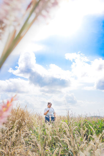 Portrait of young woman standing on grassy field against cloudy sky during sunny day