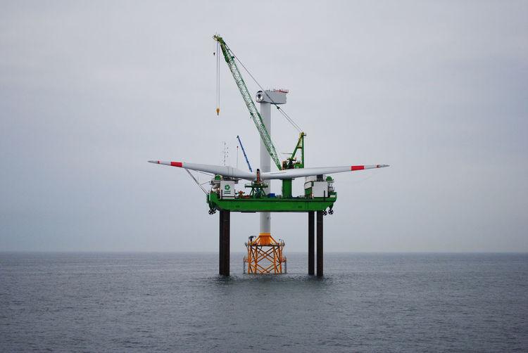 Offshore platform on sea against sky
