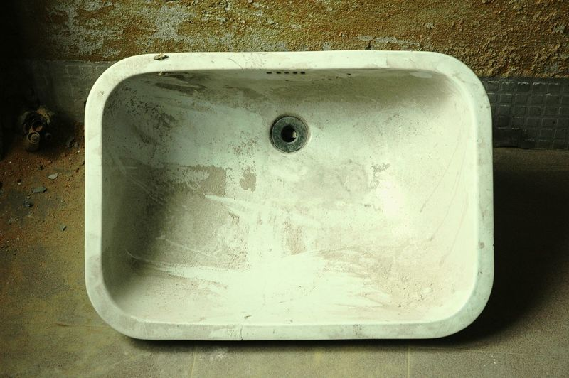 High angle view of abandoned sink by wall