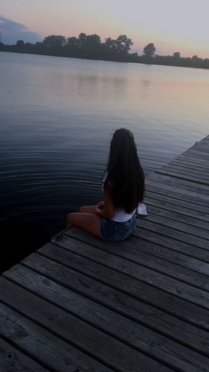 Water Lake One Person Nature Sitting Leisure Activity Tranquility Jetty Rear View Tree Outdoors Childhood Beauty In Nature Real People Sunset Day Girls Vacations Wood Paneling Sky