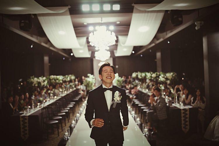 Smiling Man Wearing Suit Walking In Illuminated Room