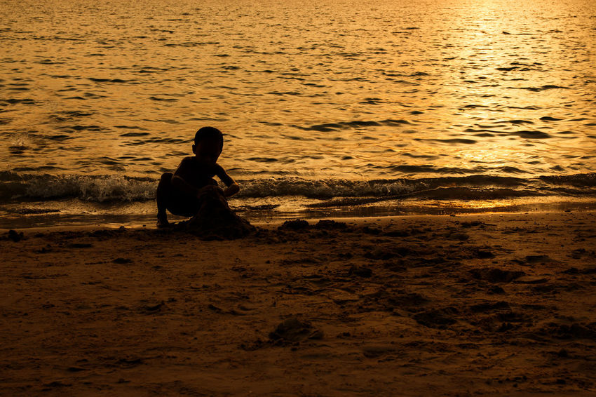 silhouette of people at the beach,The beauty of natural light at sunset. Water Real People One Person Sea Sunset Lifestyles Beach Land Leisure Activity Nature Beauty In Nature Men Sitting Tranquility Outdoors Silhouette Sky Sand Silhouette Happiness Happy People Holiday Relaxing Children Women Man Romantic Orange Clouds And Sky Love Family Summer Sunrise Boy Freshair Freedom Fun