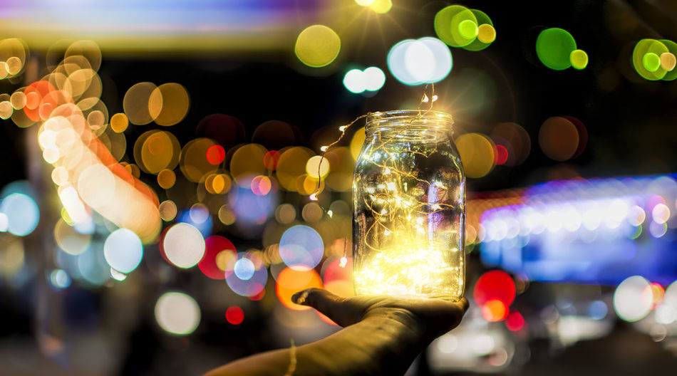 Cropped Hand Of Person Holding Illuminated Lights In Jar