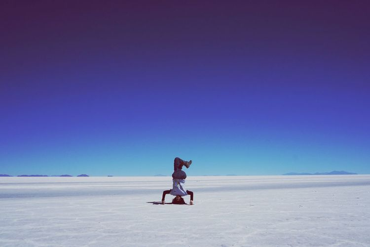 Woman Doing Handstand On Salt Flat Against Clear Blue Sky