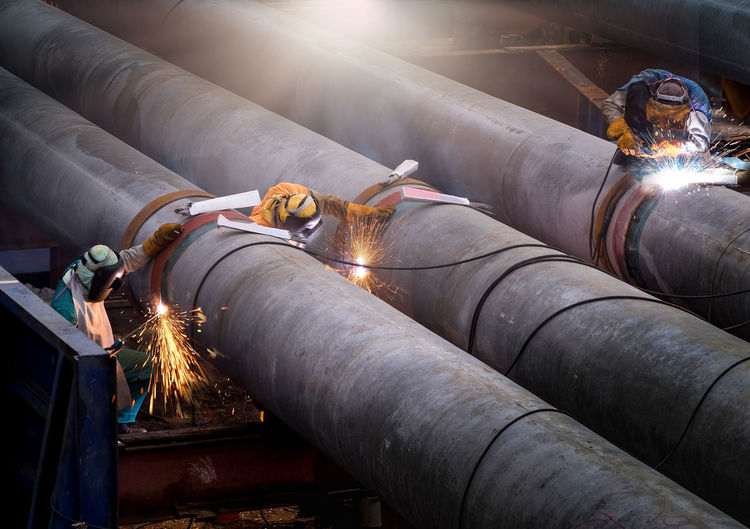Three workers welding on pipeline in factory