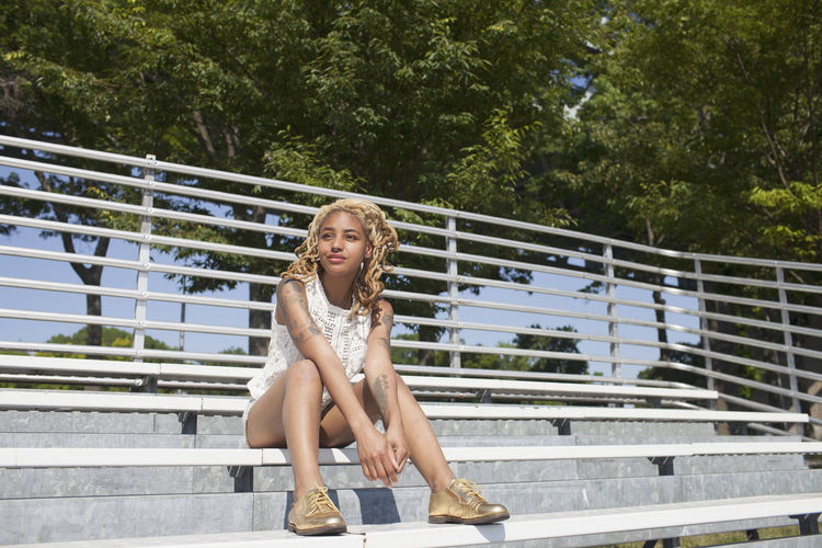 Portrait of young woman sitting on railing against trees
